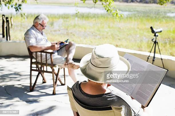 Couple reading books at safari lodge, Kafue National Park, Zambia