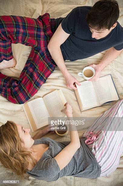 Couple reading books with coffee in bed