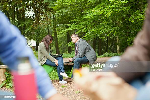 Couple reading clipboard in park
