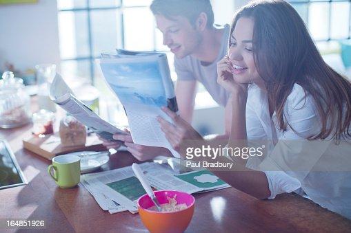 Couple reading magazines at breakfast