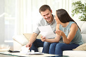 Happy couple reading mail and checking accountancy looking each other sitting on a couch at home