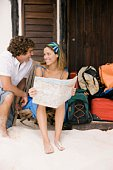 Couple reading map by beach house with luggage