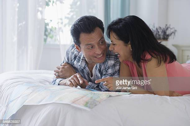 Couple reading map on bed