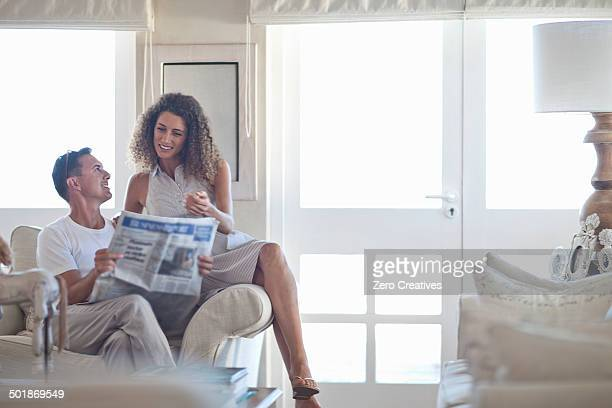 Couple reading newspaper in sitting room