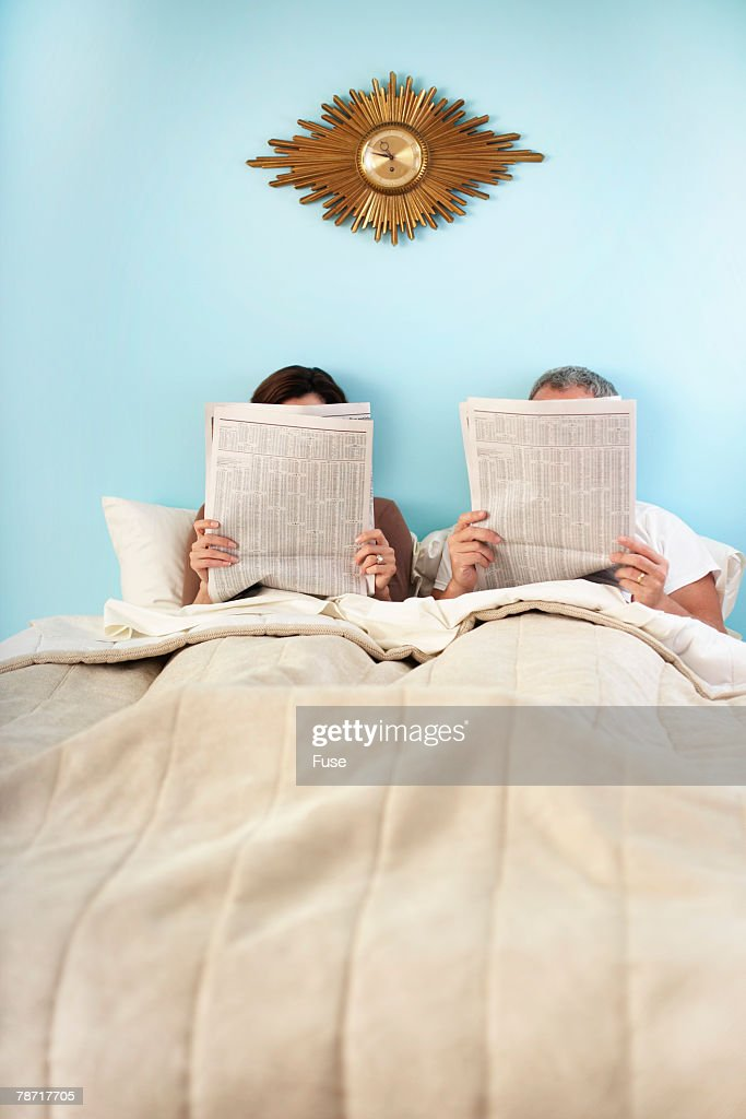 Couple Reading Newspapers in Bed : Stock Photo