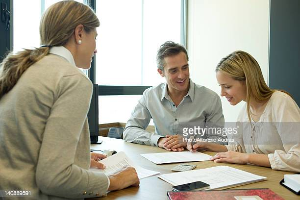 Couple reading over contract in office