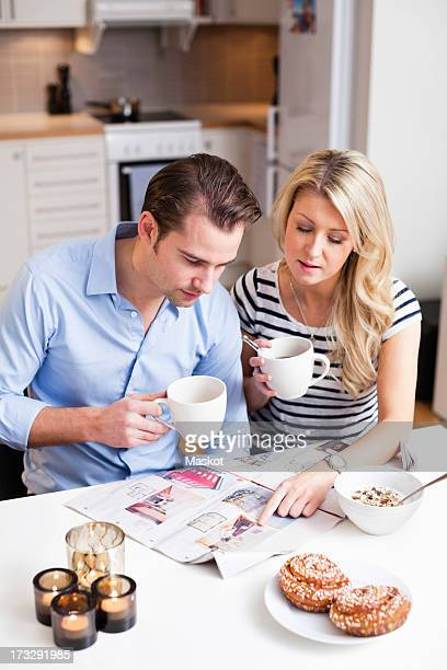 Couple reading property advertisements in newspaper while having coffee at breakfast table