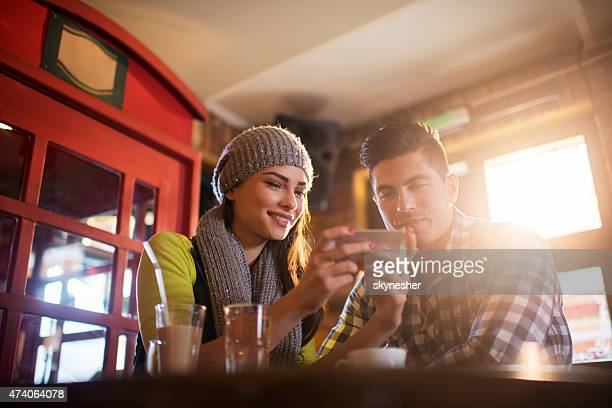 Couple reading text message on cell phone in a cafe.