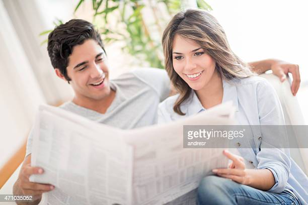 Couple reading the newspaper at home