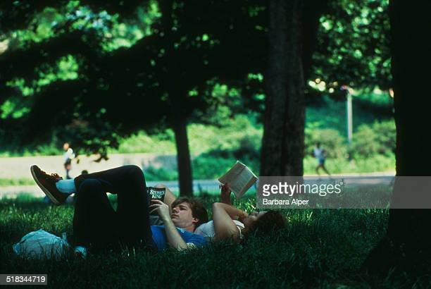 A couple reading underneath a tree in Central Park New York City USA August 1990