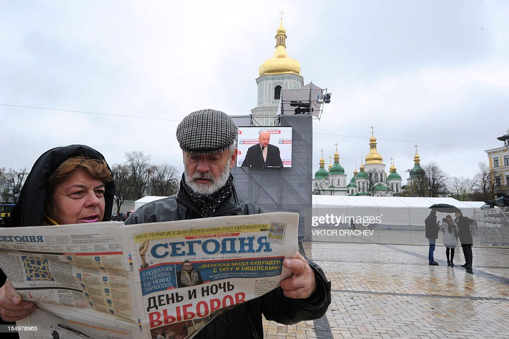 A couple reads a Ukrainian newspaper bearing headline reading 'Day and night of voting' in Kiev on October 29, 2012. Ukraine's ruling party was set on October 29, 2012 for victory against the allies of jailed ex-premier Yulia Tymoshenko after a legislative election that international observers condemned as a setback for the ex-Soviet state's nascent democracy. AFP PHOTO/ VIKTOR DRACHEV