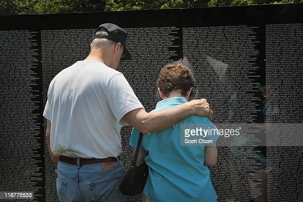 A couple reads names on the Moving Wall display a halfsize replica of the Vietnam Veterans Memorial following the opening ceremony for Welcome Home...
