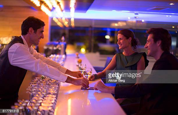 Couple receiving drinks from a barman
