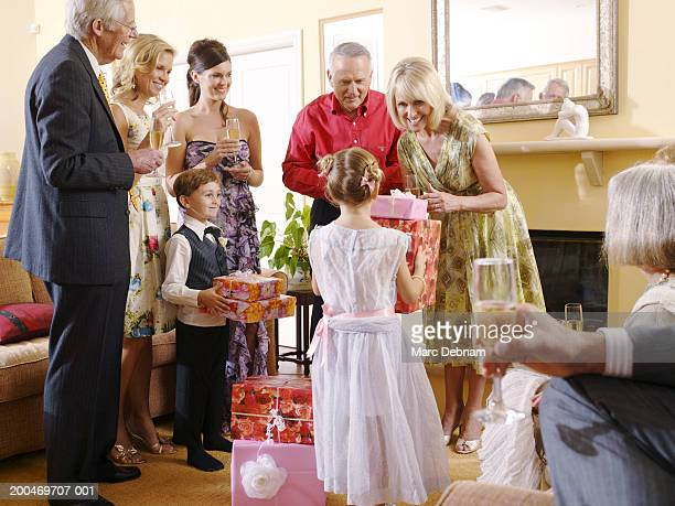 Couple receiving gifts from girl and pageboy (6-7)