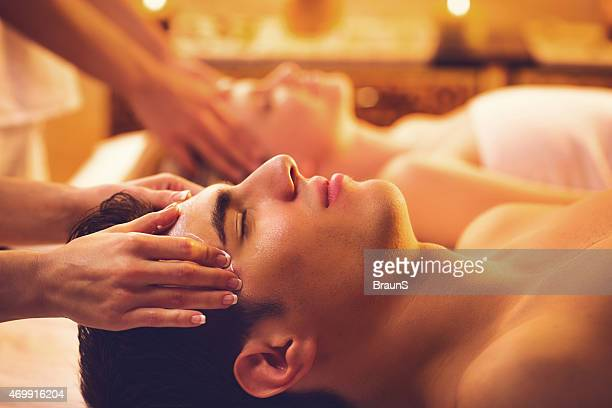 Couple receiving head massage at the spa.