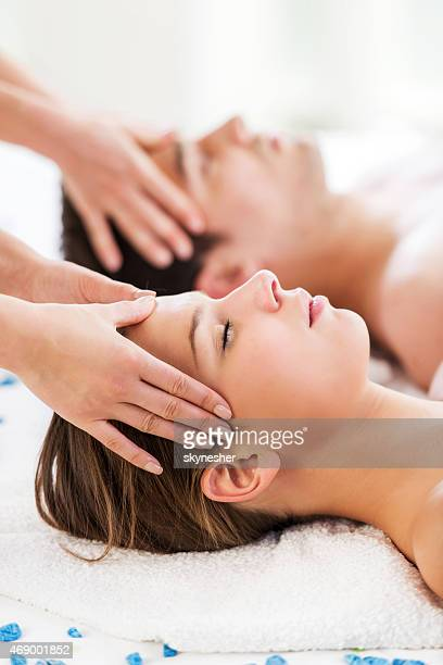 Couple receiving head massage.