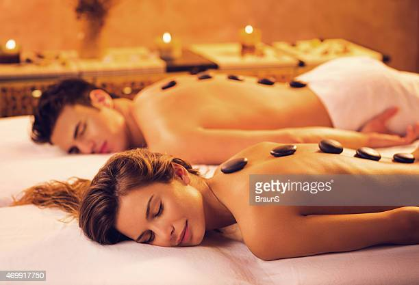 Couple receiving hot stone therapy at the spa.