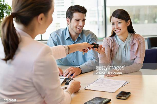 Couple receiving keys from business executive