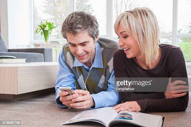 Couple reclining on floor with magazine and MP3 player
