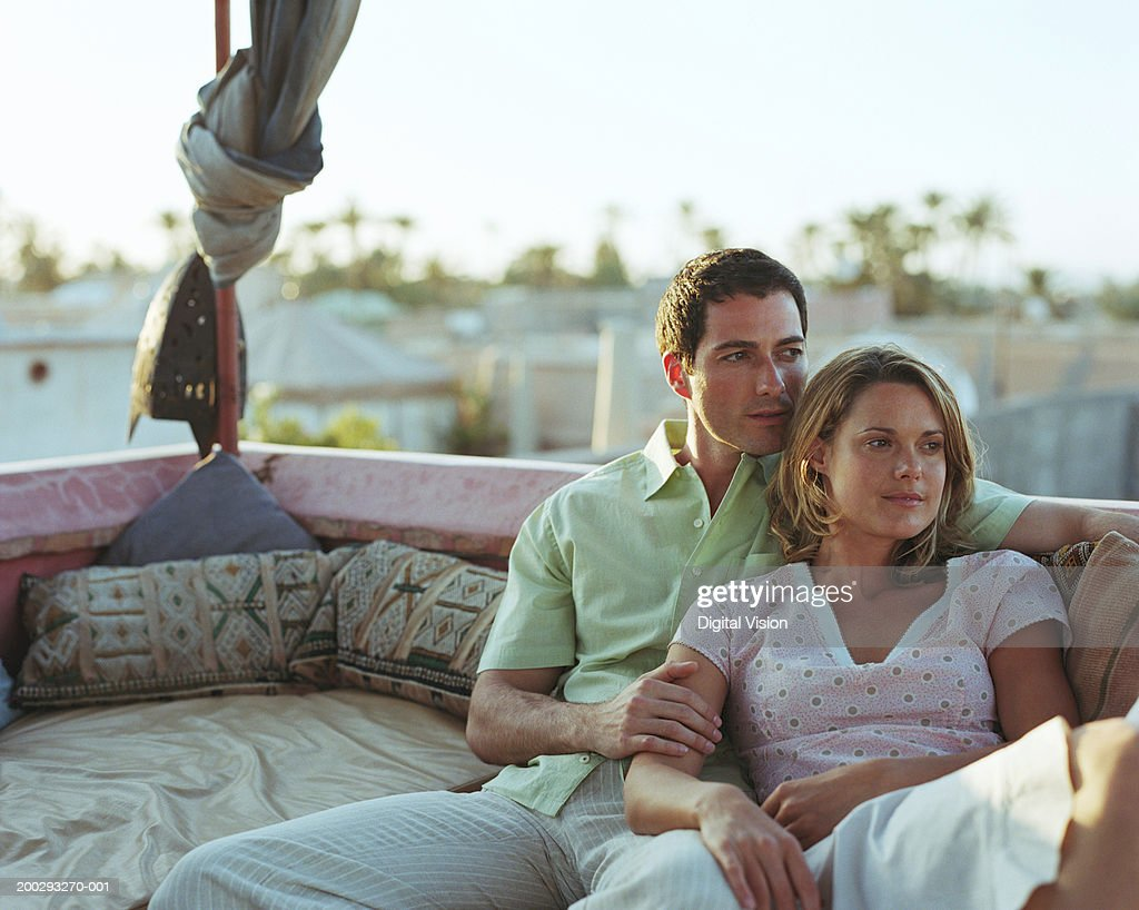 Couple reclining on seat on balcony