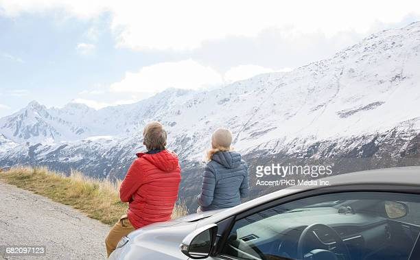 Couple relax against car, look to snowy mtns