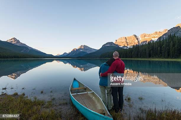 Couple relax beside canoe, mountain lake