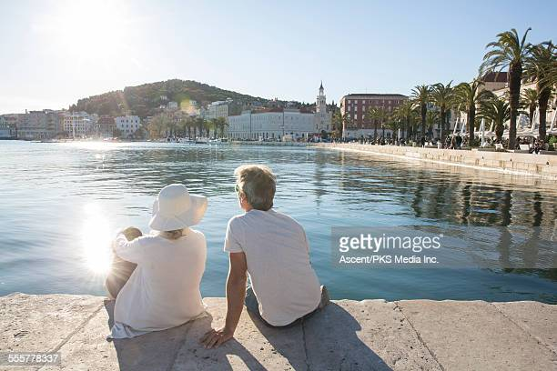 Couple relax by water's edge, on marble pier