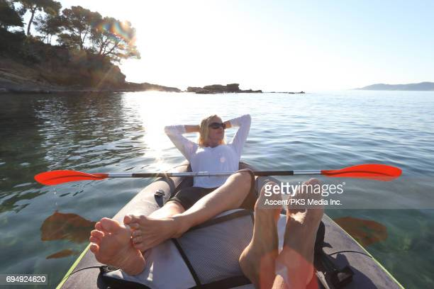 Couple relax in inflatable kayak on clear sea