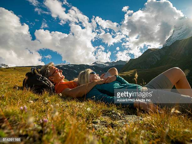Couple relax in mountain meadow, Matterhorn