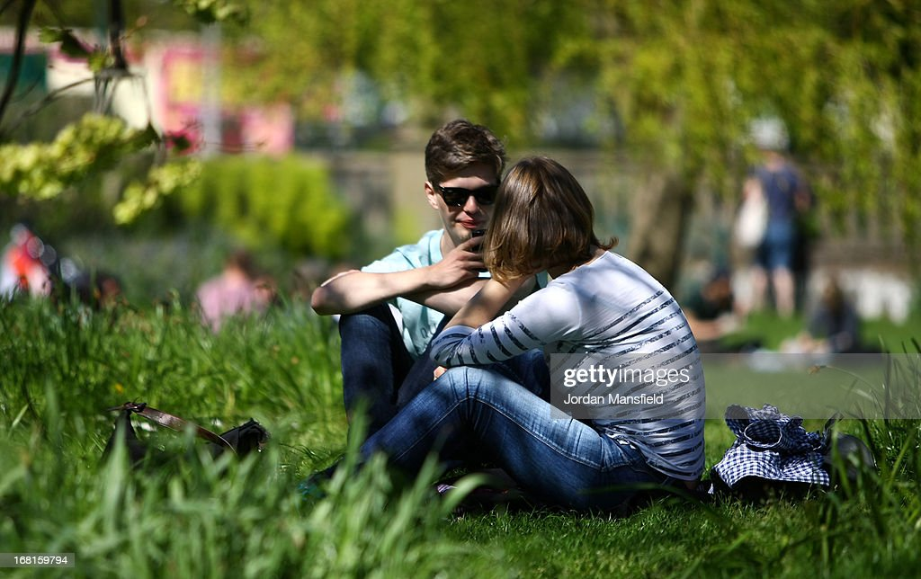 A couple relax in the sun in the Pavilion Gardens on May 6, 2013 in Brighton, England. Visitors have flocked to Brighton Beach as the Met Office predicted the May Day Bank Holiday to be the hottest day of the year so far.