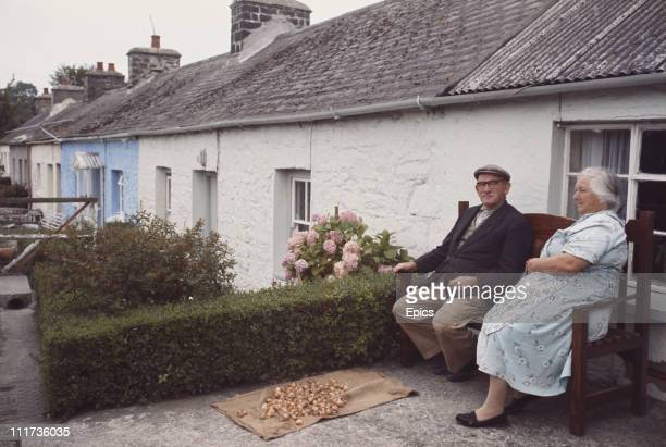 A couple relax on a bench outside their stone terraced home in Aberdaron Gwynedd Wales circa 1970