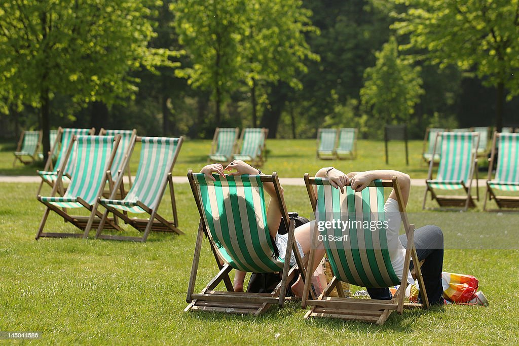A couple relax on deckchairs in the sunshine in Hyde Park on May 23 2012 in London England Following the high afternoon temperatures in the capital...