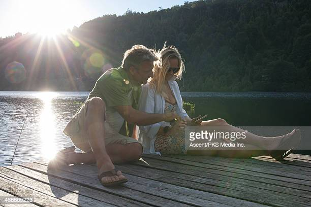 Couple relax on lake pier, use digital tablet
