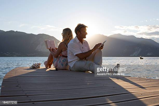 Couple relax on lake pier with book,digital tablet