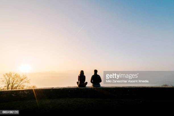 Couple relax on stone wall above valley, sunrise
