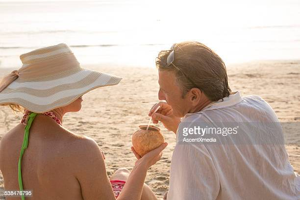 Couple relax on tropical beach, woman holds coconut for man
