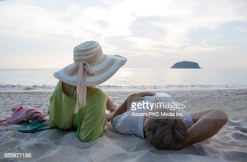 Couple relax on white sand beach, look off : Stock Photo