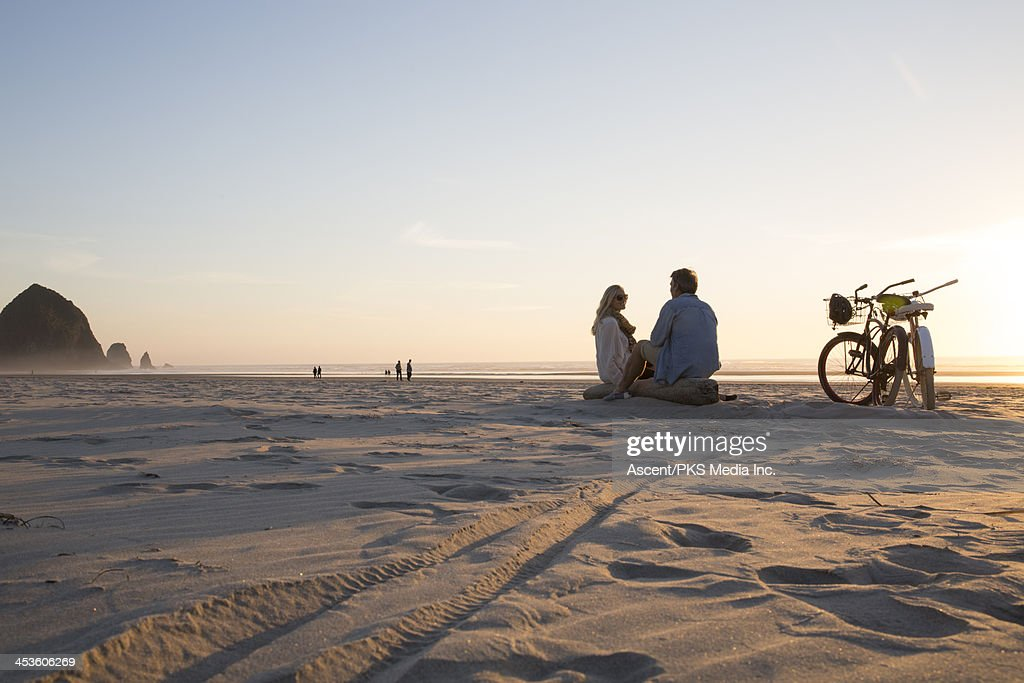 Couple relax with bicycles at beach,tracks in sand