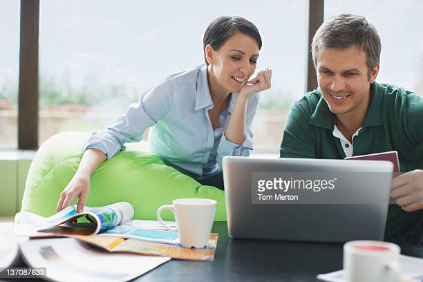 Couple relaxing and sharing laptop