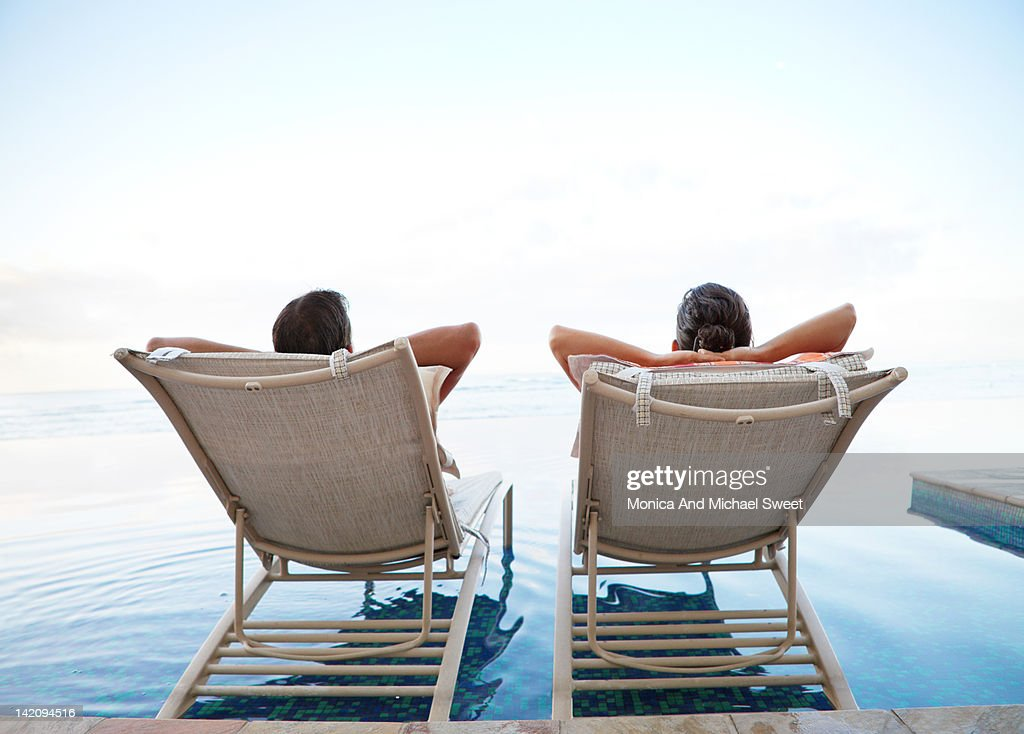 Couple relaxing at infinity pool : Stock Photo