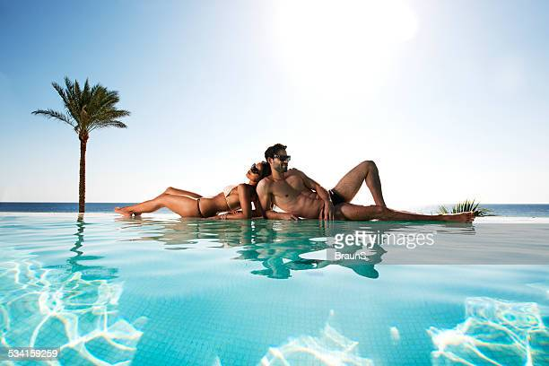 Couple relaxing at infinity pool.