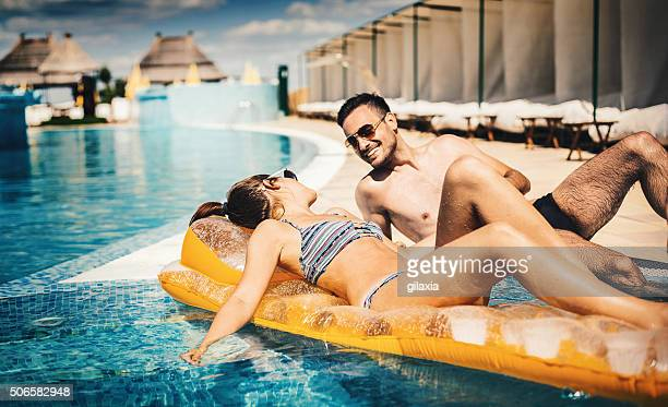 Couple relaxing at swimming pool.