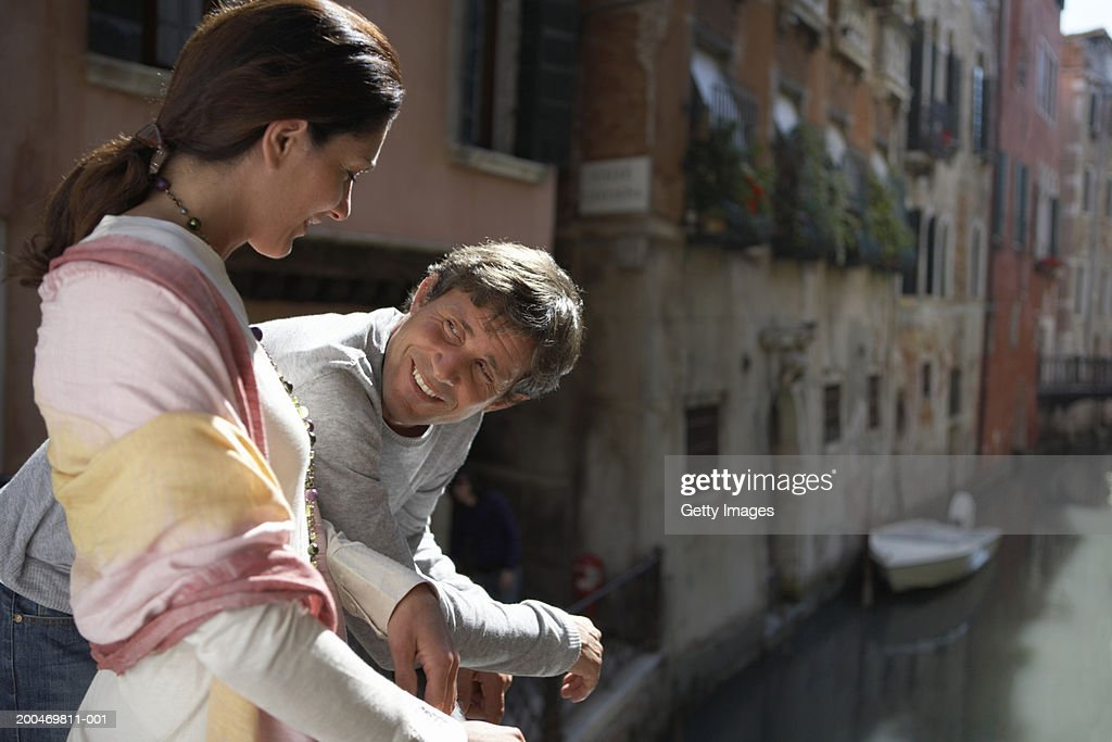 Couple relaxing beside canal, smiling at each other : Stock Photo