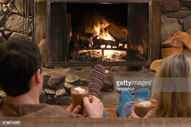 Couple relaxing by a fire