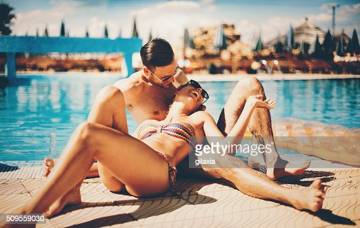 Couple relaxing by swimming pool.