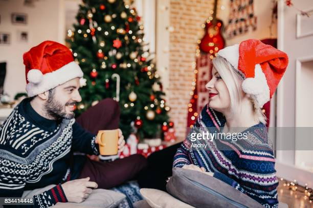 Couple relaxing by the Christmas tree, drinking hot beverages