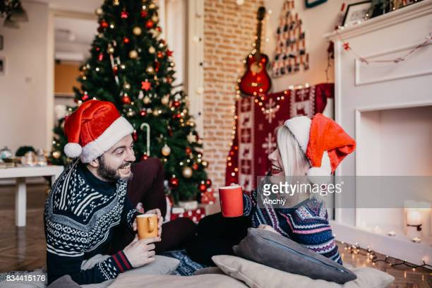 Couple relaxing by the Christmas tree, drinking hot tea