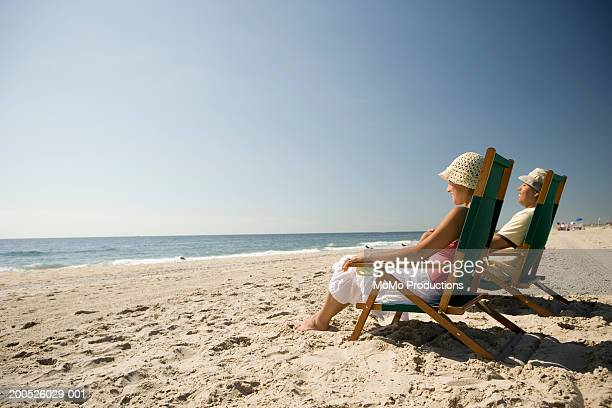 Couple relaxing in beach chairs, side view