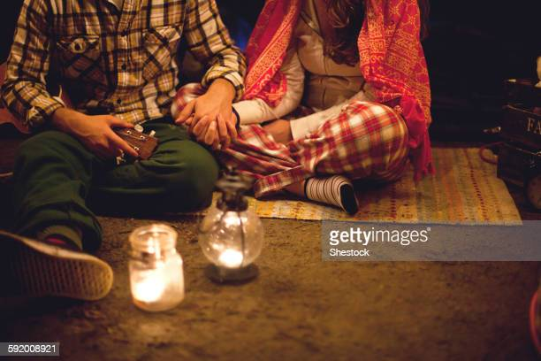 Couple relaxing in camping tent at night