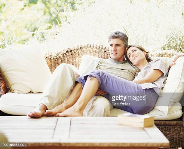 Couple relaxing in conservatory, woman resting head on man's shoulder